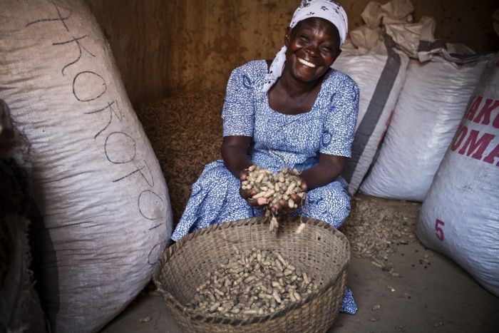Fati, a farmer from northern Ghana, sits smiling with her harvest